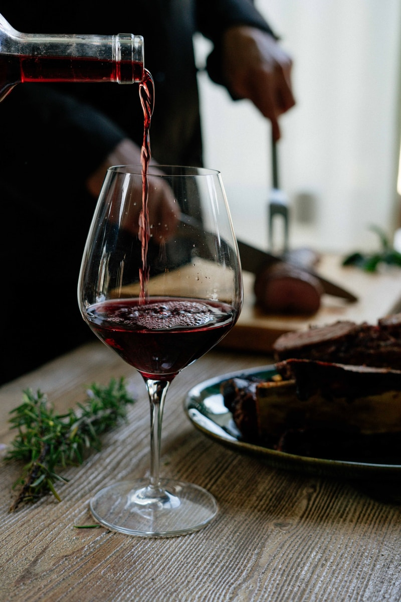 person pouring red wine on wine glass